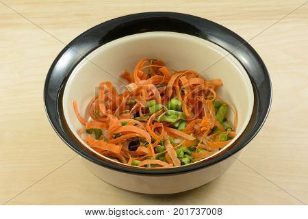 Healthy low calorie dog treat of carrot peels and ends of green beans in dog food bowl