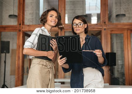 Dialogue of two pretty young women in co working office