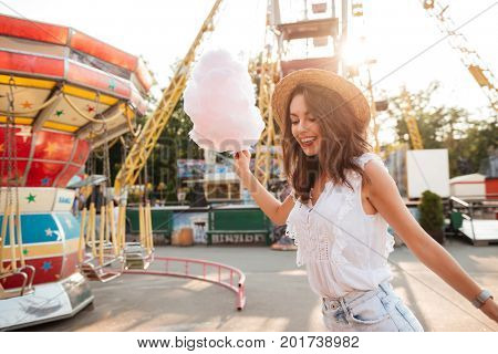 Happy smiling girl with cotton candy having fun at the amusement park