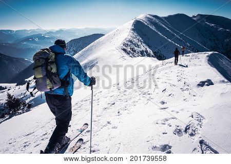 Skialpinists on snowy mountains, Skialpinists group in european alps, Symbol winter sports, Group skialpinists mountains, Group of skiers on mountain top, Concept winter adventure
