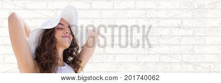 Digital composite of Portraiture of woman in summer hat relaxing against white brick wall