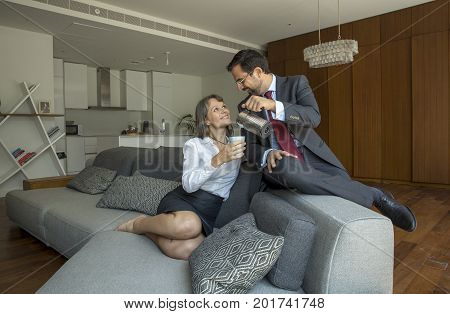 Middle Aged Couple In Formalware In Their City Apartment With A Man Serving Coffee To A Woman