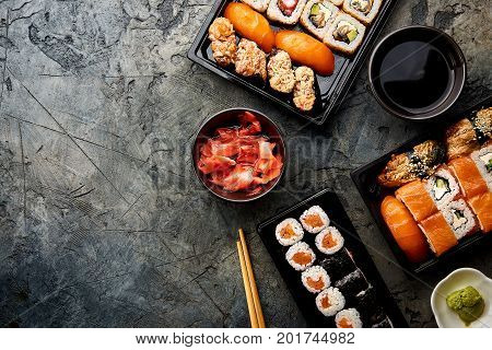 Variation of sushi and rolls on stone table. Sushi rolls, sashimi set. Top view with copy space.