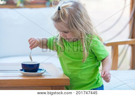 Child boy with blond long hair mixing sugar with teaspoon. Little kid boy making tea. Boy child mixing sugar in blue cup. Healthy breakfast for child. Childhood and baby care concept.