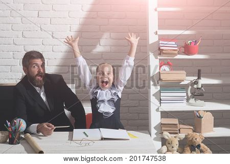 Family Sits By Desk With School Supplies. Girl And Father