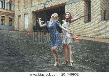 Women are happy with the rain they are happy and dancing in the rain.