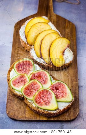 Toasted sandwiches with cream cheese fresh ripe green and red figs and peaches. Drizzled with honey. Wholegrain rye bran bread on wood cutting board grey concrete background