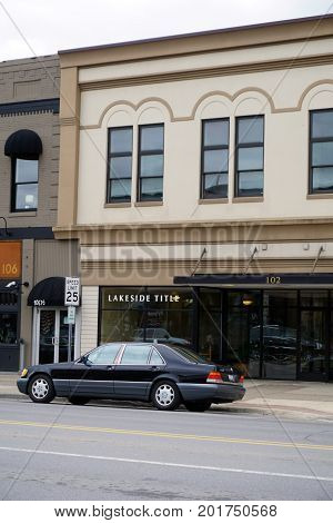 CADILLAC, MICHIGAN / UNITED STATES - MAY 31, 2017: A black Mercedes-Benz S420 luxury sedan is parked in front of Lakeside Title, on Mitchell Street in Downtown Cadillac.