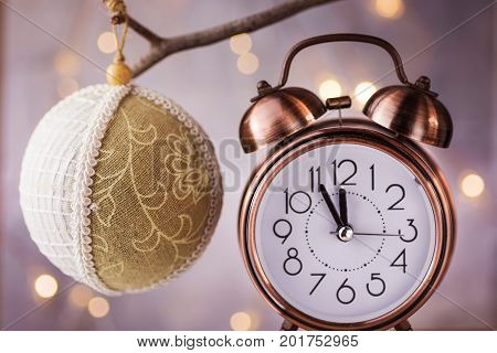 Vintage copper alarm clock showing five minutes to midnight New Year countdown. Handmade linen fabric and lace ball ornament hanging on branch. Glittering garland lights.