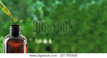 Dropper over essential oil bottle on green background