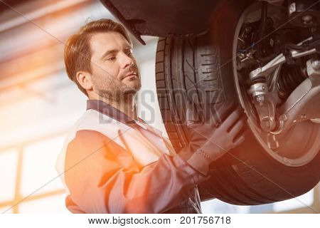 Mid adult technician adjusting car's tire in workshop