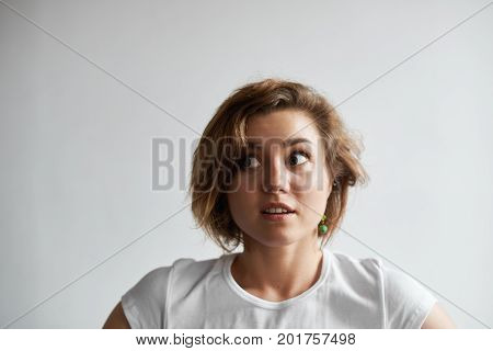 Close-up portrait of beautiful bug-eyed young Caucasian woman with short hairstyle looking sideways in shock or frustration. Human facial expressioins emotions reaction feelings and attitude
