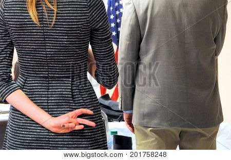 Man and female workers doing the pledge of allegiance indoors.