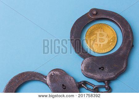 Handcuffs with coin bitcoin and punishment for the crime. Empty space for text
