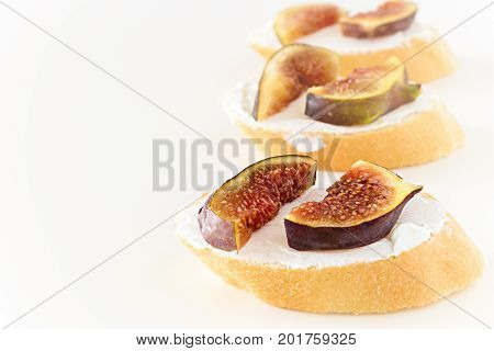 Toast Bruschetta With Fresh Figs And Goat Cheese On White Background. Shallow Depth Of Field. Select