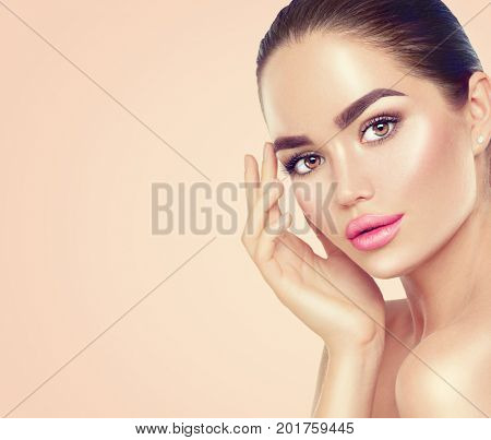 Beauty Portrait. Beautiful Spa Brunette Woman Touching her Face. Perfect Fresh Skin. Pure Beauty Model Girl. Youth and Skin Care Concept. On pink and beige background