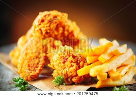 Fried chicken wings and legs with french fries on wooden table. Breaded Crispy fried kentucky chicken tasty dinner with fried potato