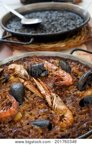 closeup of some paelleras, the paella pan, with a typical spanish seafood paella and an arroz negro or black paella, made with squid ink, on a table set for lunch
