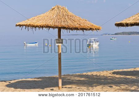Thatched sunshade on a beach reserved for you in Macedonia, Greece