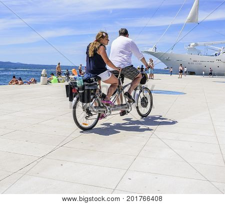 ZADAR, CROATIA - JULY 15, 2017: Tourists on a bicycle tandem ride along the waterfront.