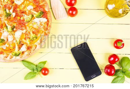 Fresh baked pizza and smartphone on wooden table with copy space. Italian cuisine delivery - phone or online order