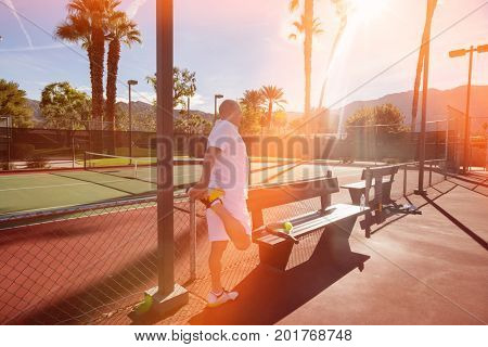 Senior male tennis player stretching leg on court