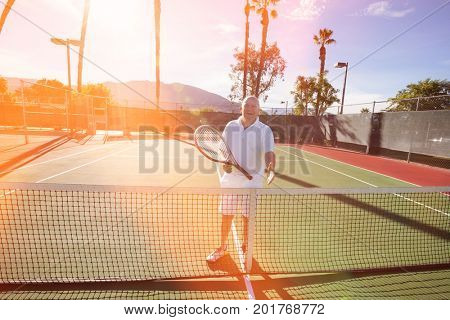 Portrait of senior tennis player offering handshake on court
