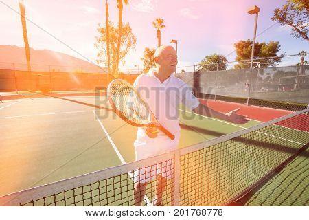 Happy senior male tennis player offering handshake on court
