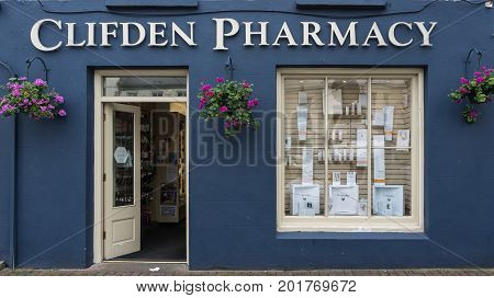 Clifden Ireland - August 4 2017: The dark blue facade of the small business pharmacy with white trim open door and display window. Street scene and flowers on the wall.