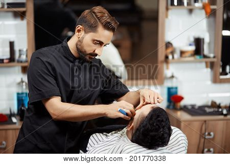 Young professional and handsome hairstylist in black suite cutting bread of client, who sitting at chair in modern barber shop against mirror. Stylist doing haircut at beauty salon. poster