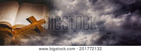 Digital composite of Cross on bible and storm cloud transition