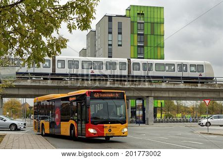 COPENHAGEN, DENMARK - NOVEMBER 5, 2016: Public bus and metro train in Amager Vest district. The public transportation in Copenhagen is very reliable, punctual, and it may takes you everywhere