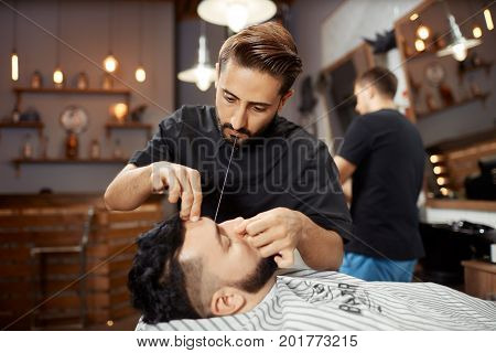 Hairdresser working at barbershop, correcting and cutting bread with white thread. Handsome hairstylist caring about face of client and doing hair removal. Beauty salon for man.