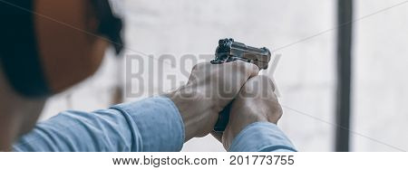 Shooting with a pistol. Man aiming pistol in shooting range. shooting range.