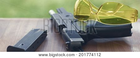 Handgun With Safety Glasses On A Wooden Background.
