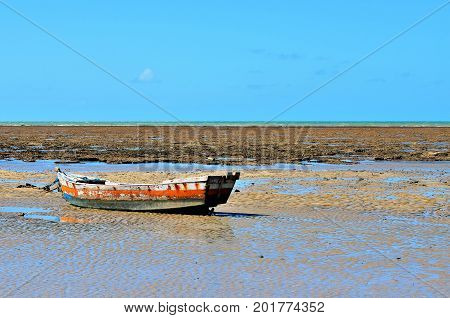 Small boat stranded during low tide with coral reef in the background in Porto Seguro, Bahia, Brazil.