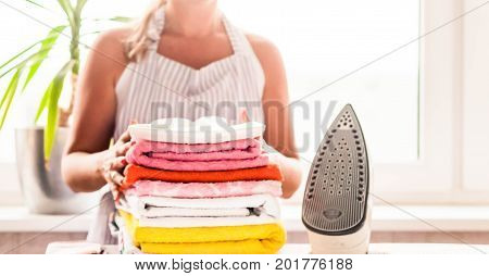 Ironing clothes on ironing board, ironed clothes ironing, laundry, clothes, housekeeping and objects concept