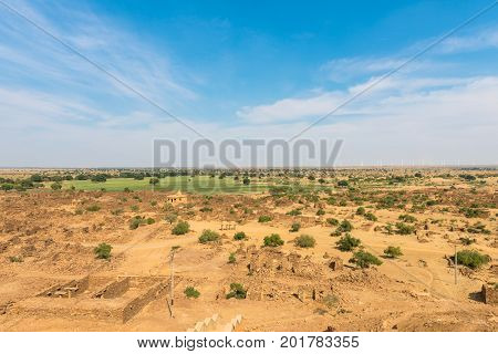 Wide angle picture of Thar Desert with old buildings located close to Jaisalmer the Golden City in India.