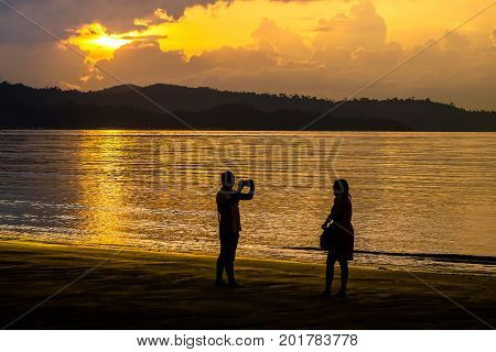 Kota Kinabalu,Sabah-Aug 8,2017:Silhouette of people taking photo with smart phone camera enjoying sunset scenery at Kota Kinabalu beach,Sabah.Smart phone camera are getting better all the time at taking photos with big megapixel.
