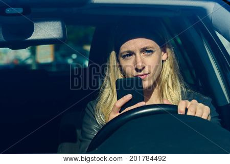 Young Woman Texting While Driving Car