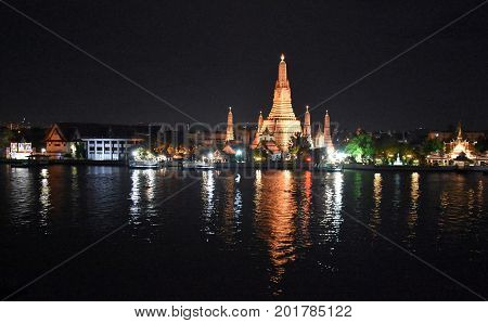 Wat Arun (Temple of Dawn) in sunset time Bangkok Thailand. Large temple Wat Arun after sunset seen accross river Chao Phraya.