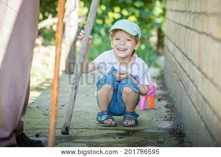 Cute little boy playing with stick outdoors grandfather standing beside him