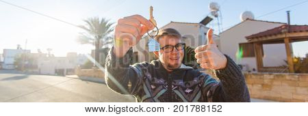 Young man holding house keys on house shaped keychain in front of a new home