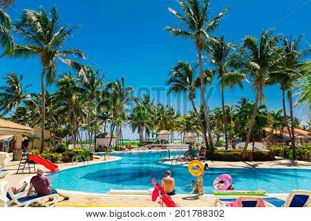 Cayo Coco island, Cuba, Sol Cayo Guillermo, July 11, 2017, view from the hotel lobby side on inviting tropical garden swimming pool with people and children enjoying their time