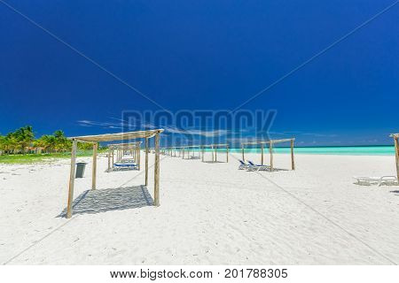 stunning, beautiful, inviting view of a wide open white sand cozy beach at Cuban Cayo Coco island on sunny gorgeous day with dark deep blue sky background