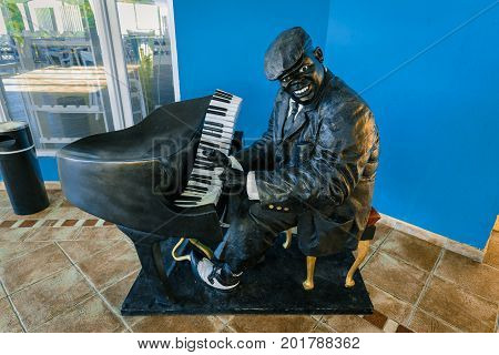 Cayo Coco island, Cuba, hotel Trip Cayo Coco, July 11, 2017, smiled, inspired black musician man sculpture playing piano against blue wall background