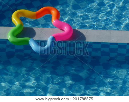 multicolored star shaped float floating on a blue pool
