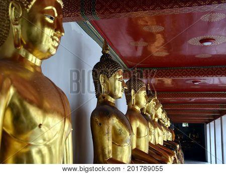 Bangkok Thailand - Aug 4 2017. Row of golden Buddha statues in Wat Pho.Bangkok Thailand - Aug 4 2017. Golden Buddha statue in Wat Pho. Wat Pho is a Buddhist temple complex with Reclining Buddha.