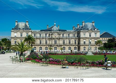Paris France - August 14 2016: The Luxembourg garden covers 23 hectares and is known for the Luxembourg palace its lawns tree-lined promenades flowerbeds the model sailboats on its circular basin and for the picturesque Medici Fountain