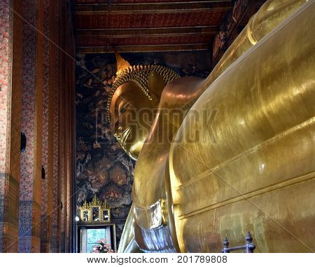 Bangkok Thailand - Aug 4 2017. Big golden Reclining Buddha in Wat Pho temple is the landmark of Bangkok Thailand and Asia. One of the oldest largest and most revered temple complexes in Bangkok.